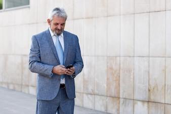 Hombre de negocios mayor texting con smartphone fuera del edificio de oficinas moderno.