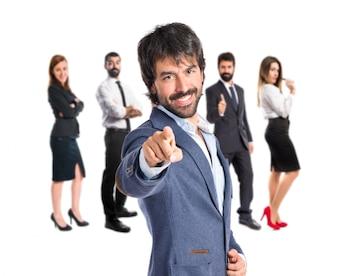 Hombre de negocios que apunta a la parte delantera sobre fondo blanco