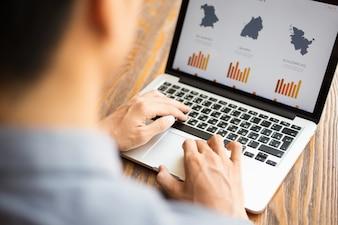Hombre de negocios que mira el informe financiero en la computadora portátil