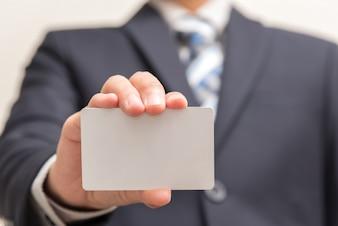 Hombre de negocios que sostiene la tarjeta en blanco blanca