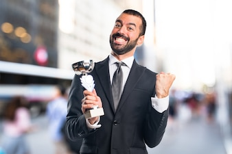 Hombre de negocios que sostiene un trofeo en fondo unfocused