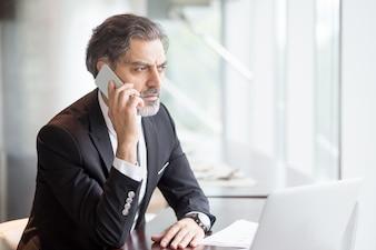Hombre de negocios serio hablando por teléfono en el escritorio