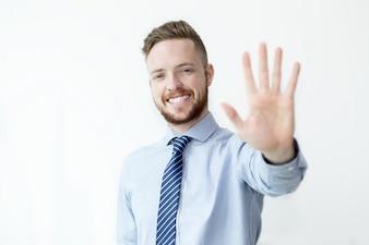 Hombre de negocios sonriente que muestra el gesto de la parada
