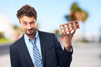 Hombre de negocios sujetando un ladrillo
