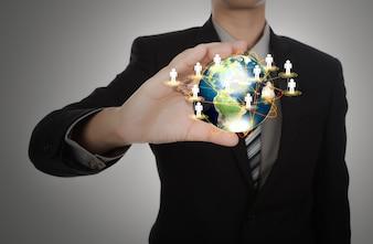 Hombre de negocios sujetando un planeta tierra con símbolos de personas
