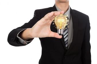 Hombre de negocios sujetando una bombilla encendida en la mano