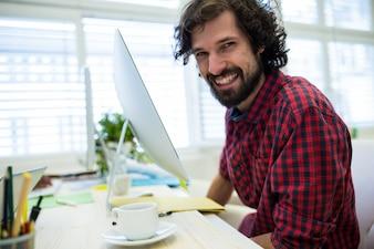 Hombre diseñador gráfico sonriendo mientras se trabaja