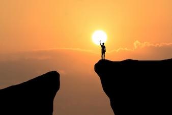 Hombre en la parte superior de la montaña, el hombre de la libertad en el fondo puesta del sol