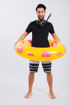 Hombre en ropa de verano con flotador y esnórquel