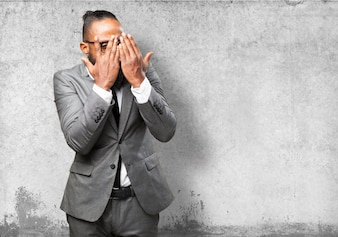 Hombre en traje cubriendo su cara