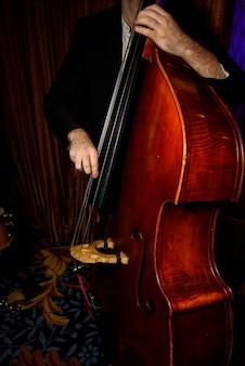 Hombre en traje negro juega en violoncelo