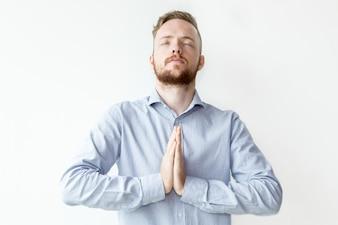 Hombre enfocado, manteniendo las manos juntas y rezando