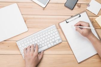 Hombre escribiendo en teclado y a mano