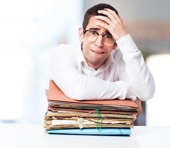 Hombre estresado mirando un montón de papeles con una mano en la frente