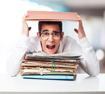 Hombre estresado mirando una montaña de carpetas y gritando