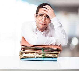Hombre estresado mirando una montaña de carpetas