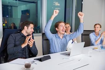 Hombre feliz celebrando con los puños en alto y sus compañeros le aplauden