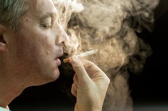 Hombre fumando contra un fondo negro, adicción al cigarrillo. Humo de la nicotina del tabaco. Insalubres, peligrosos, malos, hábitos narcóticos. Filtro blanco. Riesgo para la salud, enfermedad del cáncer. Deje de suspender la droga tóxica. Concepto de estilo de vida. Paquete en la mano