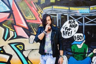 Hombre fumando un cigarro con grafitis de fondo