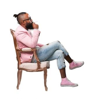 Hombre fumando un cigarro sentado en una silla