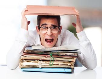 Hombre gritando con un montón de papeles