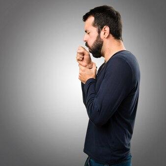 Hombre guapo con barba tosiendo mucho sobre fondo gris