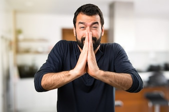 Hombre guapo con la barba que ruega dentro de la casa