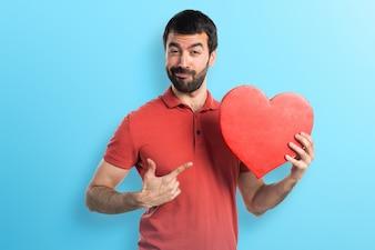 Hombre guapo con un icono del corazón en fondo colorido