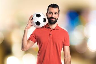 Hombre guapo sosteniendo un balón de fútbol