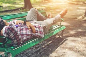 Hombre inconformista joven tumbado en el banco de parque verde, mirando a otro lado.