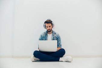 Hombre joven con ordenador portátil sentado en el suelo