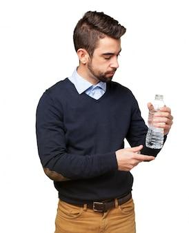 Hombre joven con una botella de agua en la mano