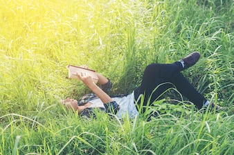 Hombre joven relajado leyendo al aire libre