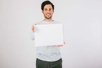 Hombre joven sonriendo con un póster en blanco