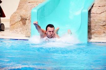 Hombre jugando en el tobogán de agua