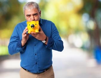 Hombre mayor con una hucha de cerdito amarilla