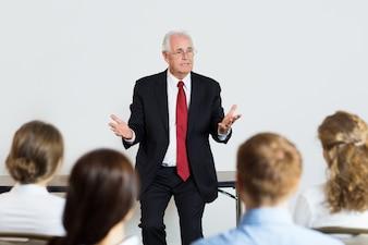 Hombre mayor de negocios dando una conferencia
