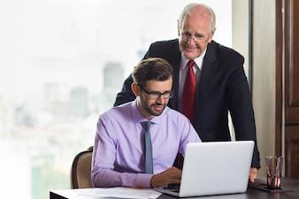 Hombre mayor de negocios mirando como trabaja otro hombre más joven