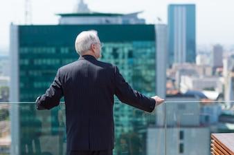 Hombre mayor de negocios mirando por una terraza