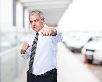 Hombre mayor en traje peleando