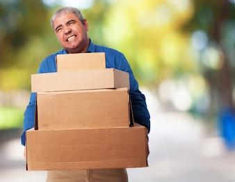 Hombre mayor haciendo esfuerzo mientras carga cajas de cartón