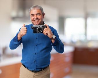 Hombre mayor sonriendo con una cámara de fotos antigua