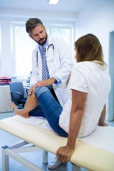 Hombre médico examinar a los pacientes de rodilla