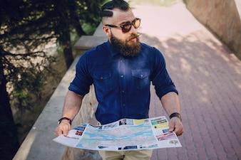 Hombre mirando a su alrededor con un mapa en sus manos