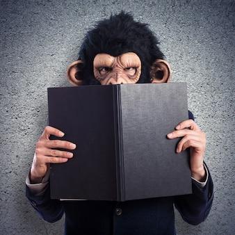 Hombre mono escondido detrás de un libro