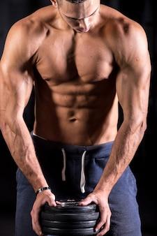 Hombre musculado con pesas