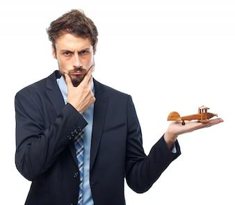 Hombre pensativo con traje jugando con un avión de madera