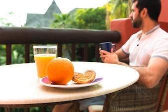 Hombre que desayuna en la terraza del hotel