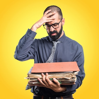 Hombre que sostiene varias notas de la universidad en fondo colorido