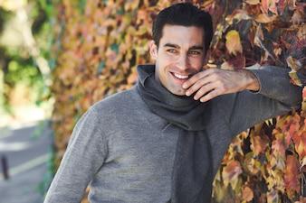 Hombre sonriendo apoyado en unos arbustos